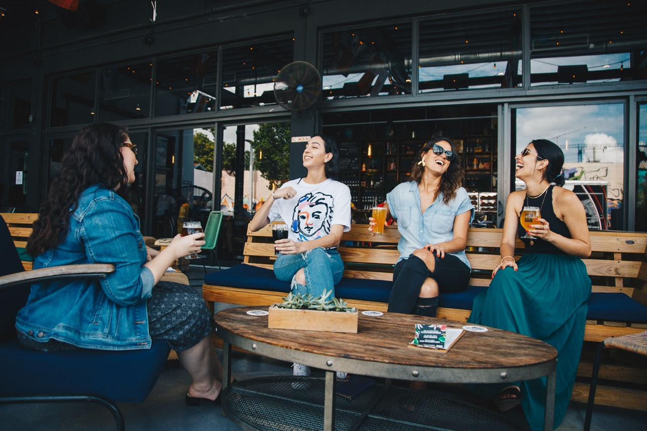 four-women-chatting-while-sitting-on-bench-1267697