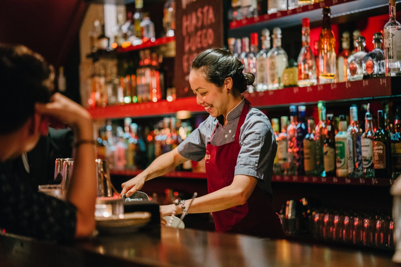 woman-bartender-smiling-while-mixing-liqueurs-1301547